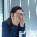 Frau reibt sich mit den Händen über müde Augen